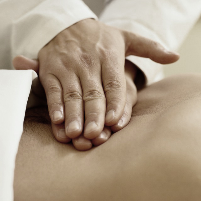 profession therapist massaging low back